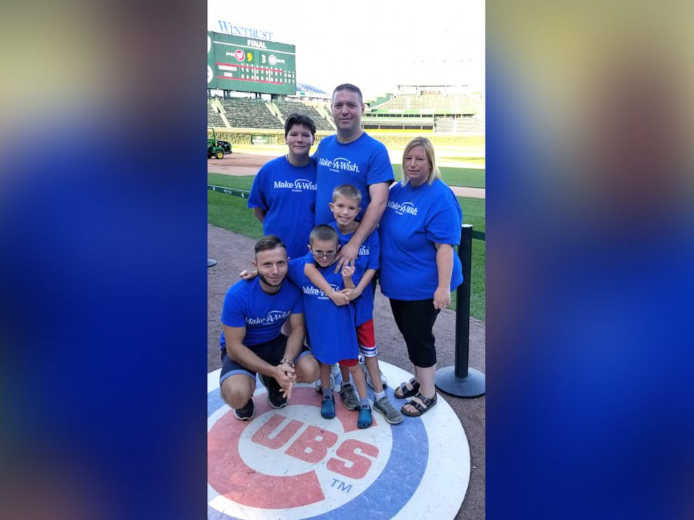 PHOTO: Dennis Gutt, kneeling, attends a Chicago Cubs game with Gabriel Smith and his family.