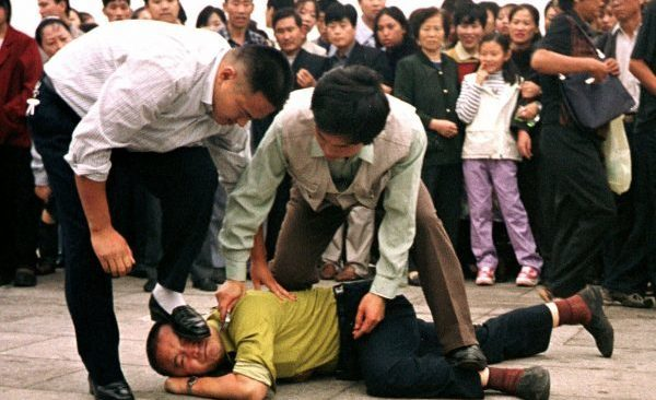 Police arrest a Falun Gong protester on Tiananmen Square in Beijing on Oct. 1, 2000. (AP Photo/Chien-min Chung)
