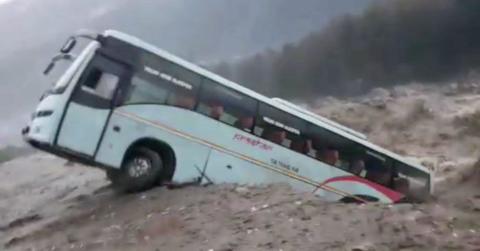 A tourist bus and other vehicles were swept away by raging flood waters in northern India.