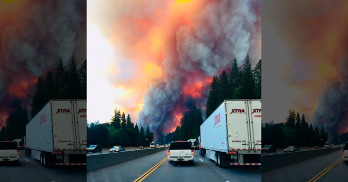 A fire rages as motorists travel on Interstate 5 near Lake Shasta, Calif