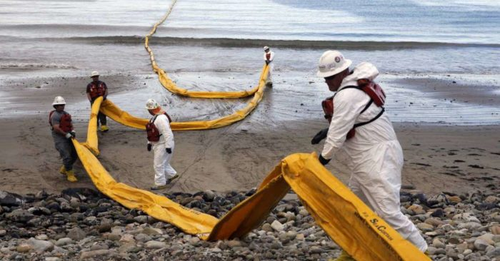 In this May 21, 2015, file photo, workers prepare an oil containment boom at Refugio State Beach, north of Goleta, Calif., two days after a ruptured pipeline created the largest coastal oil spill in California in 25 years. A California jury has found a pipeline company guilty of nine criminal charges for causing a 2015 oil spill that was the state's worst coastal spill in 25 years. The jury in Santa Barbara County reached its verdict against Plains All American Pipeline of Houston on Friday, Sept. 7, 2018, following a four-month trial.