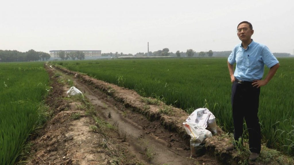 """Sun Yi and the deadly Masanjia labor camp in the background, in """"Letter From Masanjia."""" (Flying Cloud Productions)"""