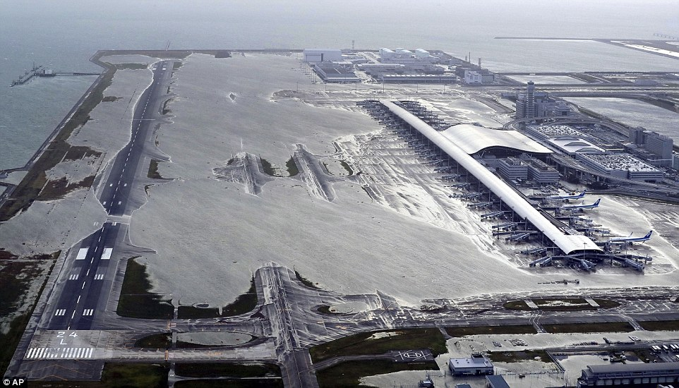 Giant waves and 135mph winds have lashed Japan today killing two and injuring dozens while more than a million people have been told to evacuate amid the worst storm to hit the country in 25 years. This was the scene as flood water covered Kansai International Airport