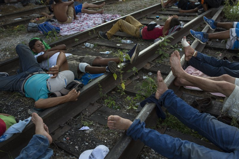 Migrants rest on the railroad rails, as a thousands-strong caravan of Central American migrants slowly makes its way toward the U.S. border, between Pijijiapan and Arriaga, Mexico, Friday, Oct. 26, 2018. On Friday, the caravan made its most ambitious single-day trek since the migrants crossed into the southern Mexican state of Chiapas a week ago, a 60-mile (100-kilometer) hike up the coast from Pijijiapan to the town of Arriaga.(AP Photo/Rodrigo Abd)