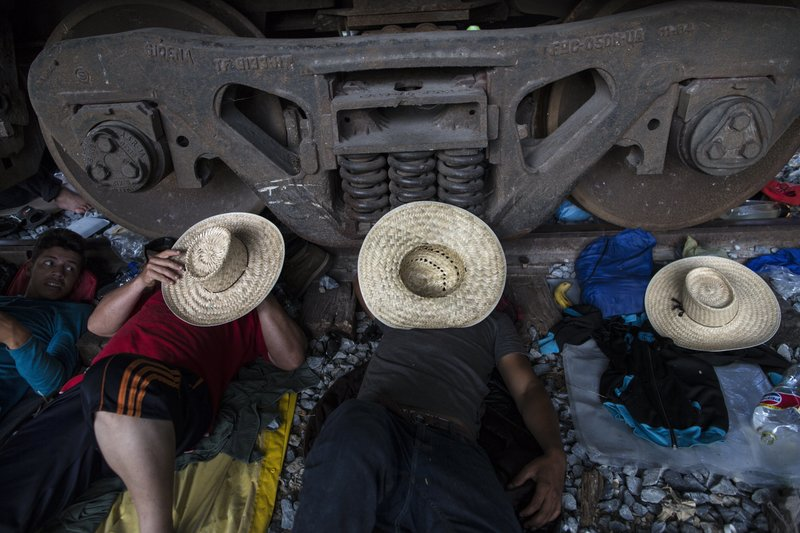 Migrants rest on the railroad rails as a thousands-strong caravan of Central American migrants slowly makes its way toward the U.S. border, between Pijijiapan and Arriaga, Mexico, Friday, Oct. 26, 2018. On Friday, the caravan made its most ambitious single-day trek since the migrants crossed into the southern Mexican state of Chiapas a week ago, a 60-mile (100-kilometer) hike up the coast from Pijijiapan to the town of Arriaga.(AP Photo/Rodrigo Abd)