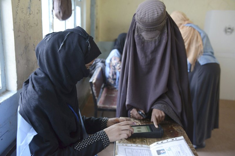 A woman voter, right, gets her finger scanned before casting her vote during parliamentary elections in Kandahar, south of Afghanistan, Saturday, Oct. 27, 2018. Security was tight in southern Kandahar on Saturday as voters went to the polls in parliamentary elections that were delayed in the province by one week after an attack by an elite guard killed two top government officials, including a powerful provincial police chief. (AP Photo)