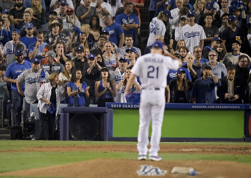 Fans cheer for Los Angeles Dodgers starting pitcher Walker Buehler after the last out in the top of the seventh inning in Game 3 of the World Series baseball game against the Boston Red Sox on Friday, Oct. 26, 2018, in Los Angeles. (AP Photo/Mark J. Terrill)