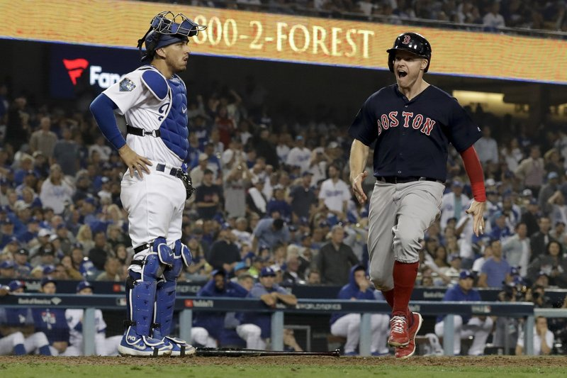 Boston Red Sox's Brock Holt scores past Los Angeles Dodgers catcher Austin Barnes on a fielding error by Scott Alexander during the 13thinning in Game 3 of the World Series baseball game on Friday, Oct. 26, 2018, in Los Angeles. (AP Photo/David J. Phillip)