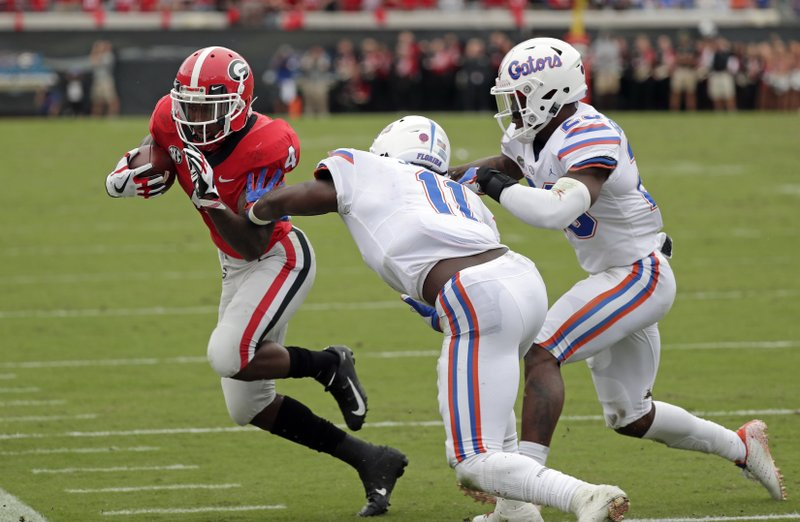 Florida linebacker Vosean Joseph (11) and defensive back Chauncey Gardner-Johnson force Georgia wide receiver Jayson Stanley out of bounds at the 4-yard line during the final moments of the first half of an NCAA college football game Saturday, Oct. 27, 2018, in Jacksonville, Fla. (AP Photo/John Raoux)