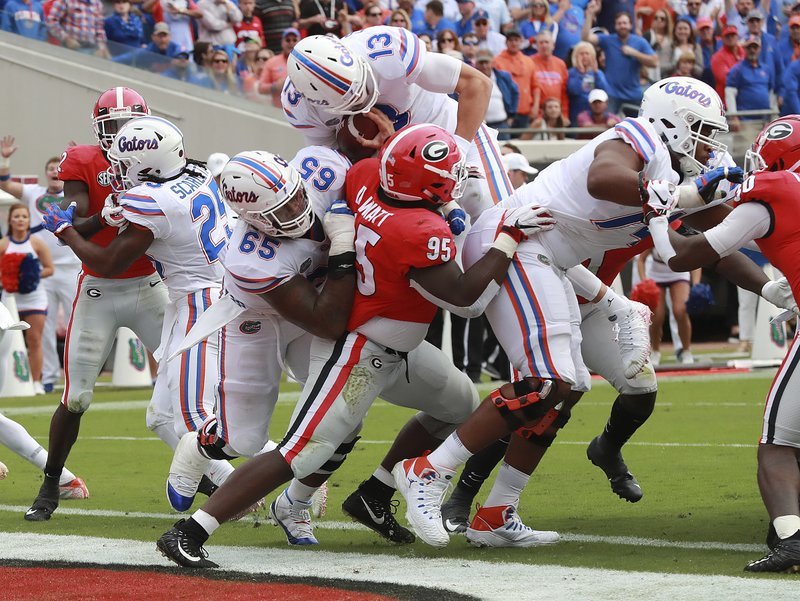 Florida quarterback Feleipe Franks (13) dives over the goal line for touchdown past Georgia defensive lineman Devonte Wyatt (95) during the first half of an NCAA college football game Saturday, Oct. 27, 2018, in Jacksonville, Fla. (Curtis Compton/Atlanta Journal-Constitution via AP)