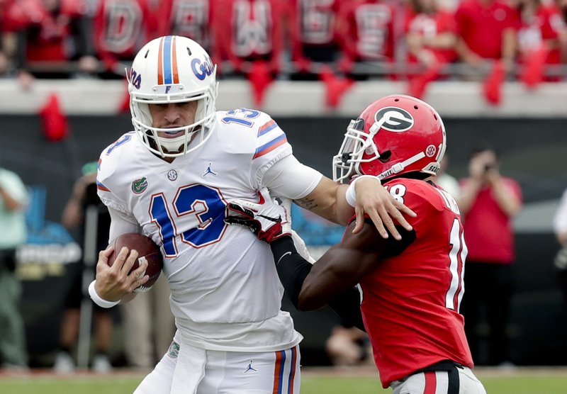 Florida quarterback Feleipe Franks (13) is stopped by Georgia defensive back Deandre Baker, right, during the first half of an NCAA college football game Saturday, Oct. 27, 2018, in Jacksonville, Fla. (AP Photo/John Raoux)