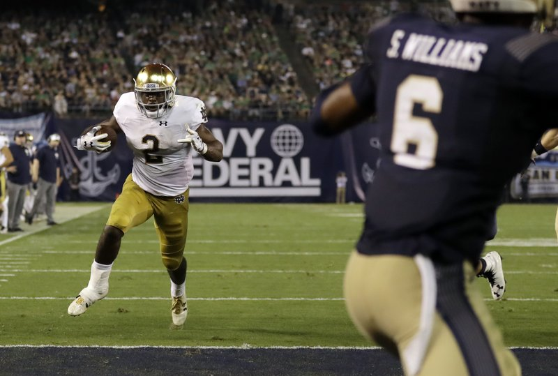 Notre Dame running back Dexter Williams (2) scores a touchdown during the first half of an NCAA college football game against Navy Saturday, Oct. 27, 2018, in San Diego. (AP Photo/Gregory Bull)