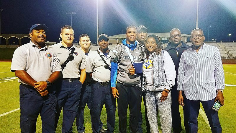 In this Oct. 19, 2018, photo Richland Northeast quarterback Josh Boyd, center, poses for a photo with his parents and members of Columbia Fire Department before a high school football game in Columbia, S.C. Boyd suffered a heart attack while playing a pick-up basketball game Oct. 10 at Sonny's SportsPlex in Columbia. Boyd was fortunate to be playing basketball that day with members of the Columbia Fire Department. Those members sprung immediately into action and were able to get him and to the hospital. (Lou Bezjak/The State via AP)