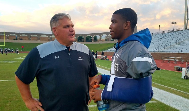In this Oct. 19, 2018, photo Richland Northeast quarterback Josh Boyd, right, talks with York coach Bobby Carroll before a high school football game in Columbia, S.C. Boyd suffered a heart attack while playing a pick-up basketball game Oct. 10 at Sonny's SportsPlex in Columbia. He had open-heart surgery two days later at MUSC in Charleston. (Lou Bezjak/The State via AP)
