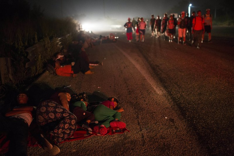 A family walks among other migrants in the Central American migrant caravan that slowly making its way toward the U.S. border, outside Arriaga, Mexico, before dawn on Saturday, Oct. 27, 2018. Many migrants said they felt safer traveling and sleeping with several thousand strangers in unknown towns than hiring a smuggler or trying to make the trip alone. (AP Photo/Rodrigo Abd)