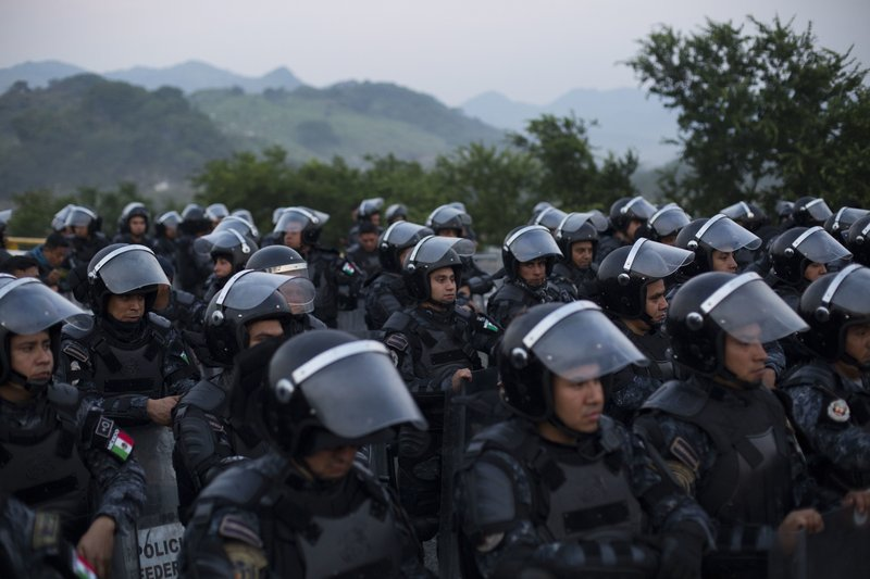 Mexican federal police in riot gear block the highway to keep a thousands-strong caravan of Central American migrants from advancing on their way to the U.S. border, outside Arriaga, Mexico, Saturday, Oct. 27, 2018. Hundreds of Mexican federal officers carrying plastic shields briefly blocked the caravan of Central American migrants from continuing toward the United States, after several thousand of the migrants turned down the chance to apply for refugee status and obtain a Mexican offer of benefits. (AP Photo/Rebecca Blackwell)