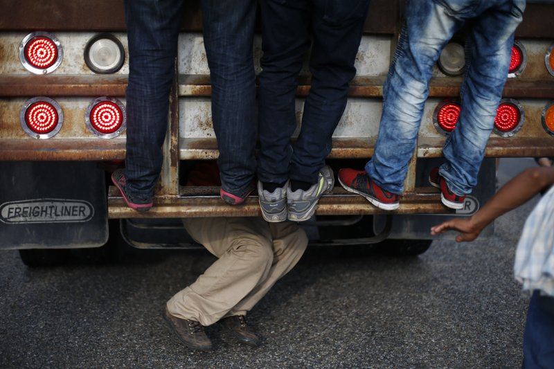 A man climbs onto the undercarriage of a moving truck, as Central American migrants hitch rides amidst a walking caravan of thousands, outside Arriaga, Mexico, Saturday, Oct. 27, 2018. Many migrants said they felt safer traveling and sleeping with several thousand strangers in unknown towns than hiring a smuggler or trying to make the trip alone.(AP Photo/Rebecca Blackwell)