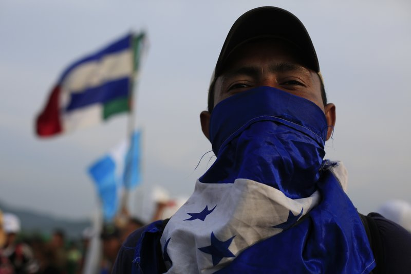 A man shields his face from the sun with a Honduran flag, as Mexico's federal police briefly blocked the highway in an attempt to stop a thousands-strong caravan of Central American migrants from advancing, outside the town of Arriaga, Mexico, Saturday, Oct. 27, 2018. Hundreds of Mexican federal officers carrying plastic shields had blocked the caravan from advancing toward the United States, after several thousand of the migrants turned down the chance to apply for refugee status and obtain a Mexican offer of benefits. (AP Photo/Rebecca Blackwell)
