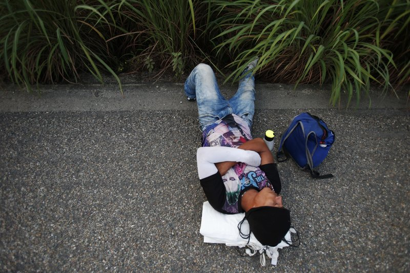 A young man rests on the side of the highway after Mexican police blockaded the road to keep them from advancing, outside the town of Arriaga, Mexico, Saturday, Oct. 27, 2018. Hundreds of Mexican federal officers carrying plastic shields briefly blocked the caravan of Central American migrants from continuing toward the United States, after several thousand of the migrants turned down the chance to apply for refugee status and obtain a Mexican offer of benefits. (AP Photo/Rebecca Blackwell)