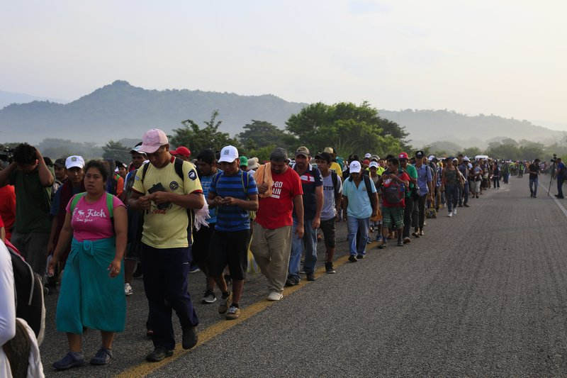 Migrants walk along the road after Mexico's federal police briefly blocked the highway in an attempt to stop a thousands-strong caravan of Central American migrants from advancing, outside the town of Arriaga, Mexico, Saturday, Oct. 27, 2018. Hundreds of Mexican federal officers carrying plastic shields had blocked the caravan from advancing toward the United States, after several thousand of the migrants turned down the chance to apply for refugee status and obtain a Mexican offer of benefits. (AP Photo/Rebecca Blackwell)