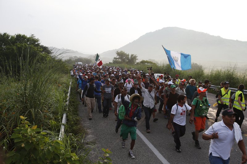 Migrants walk along the road after Mexico's federal police briefly blocked the highway in an attempt to stop a thousands-strong caravan of Central American migrants from advancing, outside the town of Arriaga, Chiapas State, Mexico, Saturday, Oct. 27, 2018. Hundreds of Mexican federal officers carrying plastic shields had blocked the caravan from advancing toward the United States, after several thousand of the migrants turned down the chance to apply for refugee status and obtain a Mexican offer of benefits. (AP Photo/Rebecca Blackwell)