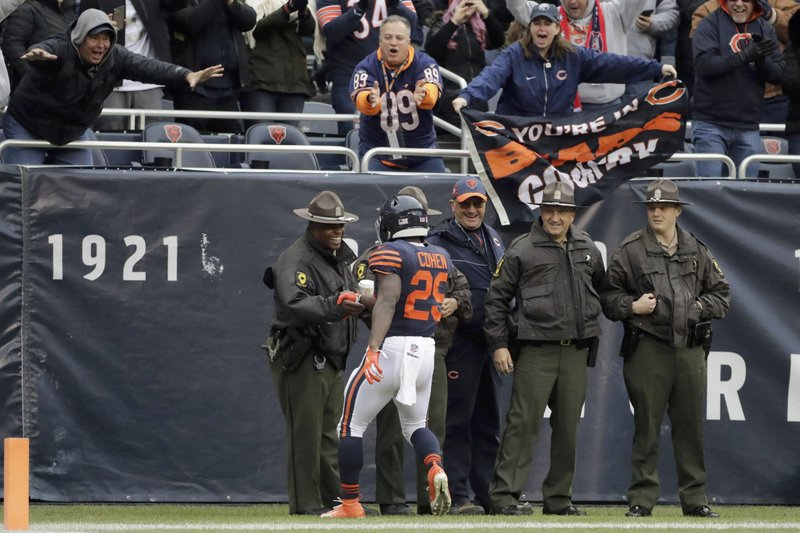 Chicago Bears running back Tarik Cohen (29) shakes hands with law enforcement officers as he celebrates a touchdown during the first half of an NFL football game against the New York Jets Sunday, Oct. 28, 2018, in Chicago. (AP Photo/Nam Y. Huh)