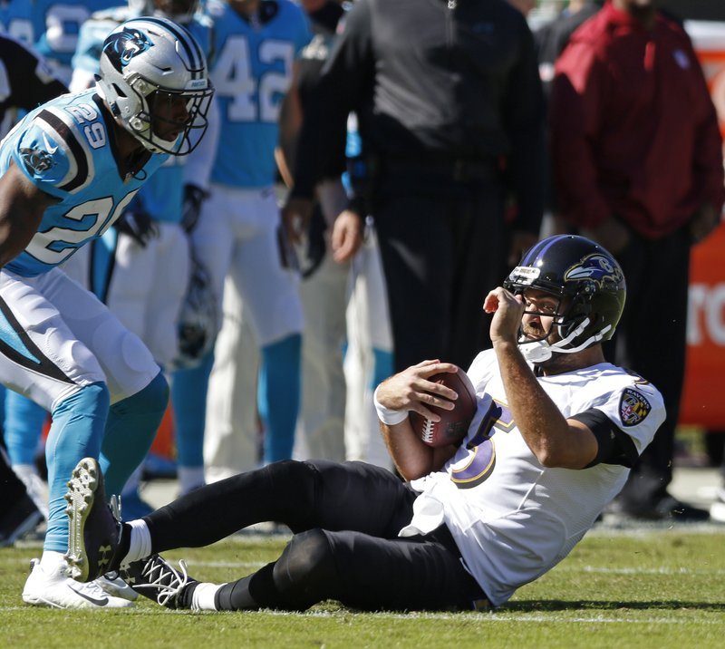 Baltimore Ravens' Joe Flacco (5) slides as Carolina Panthers' Eric Reid (25) defends in the first half of an NFL football game in Charlotte, N.C., Sunday, Oct. 28, 2018. (AP Photo/Nell Redmond)