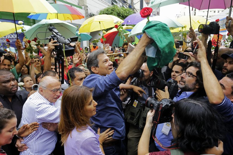 Workers' Party presidential candidate Fernando Haddad holds a Brazilian flag after casting his vote in the presidential election in Sao Paulo, Brazil, Sunday, Oct. 28, 2018. Brazilian voters decide Sunday who will next lead the world's fifth-largest country, the left-leaning Haddad or far-right rival Jair Bolsonaro. (AP Photo/Nelson Antoine)