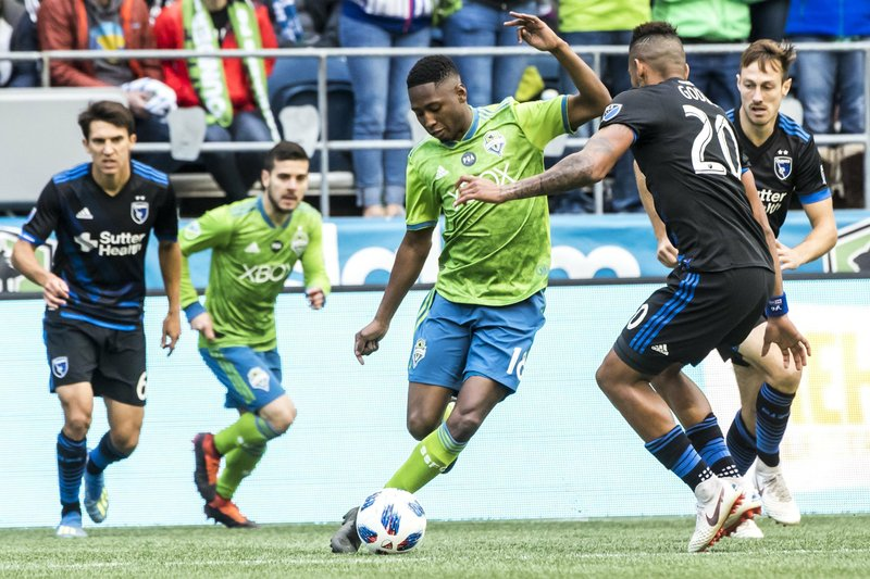 Seattle Sounders defender Kelvin Leerdam, center, maneuvers around San Jose Earthquakes midfielder Anibal Godoy in the first half of an MLS soccer game in Seattle, Sunday, Oct. 28, 2018. (Bettina Hansen/The Seattle Times via AP)