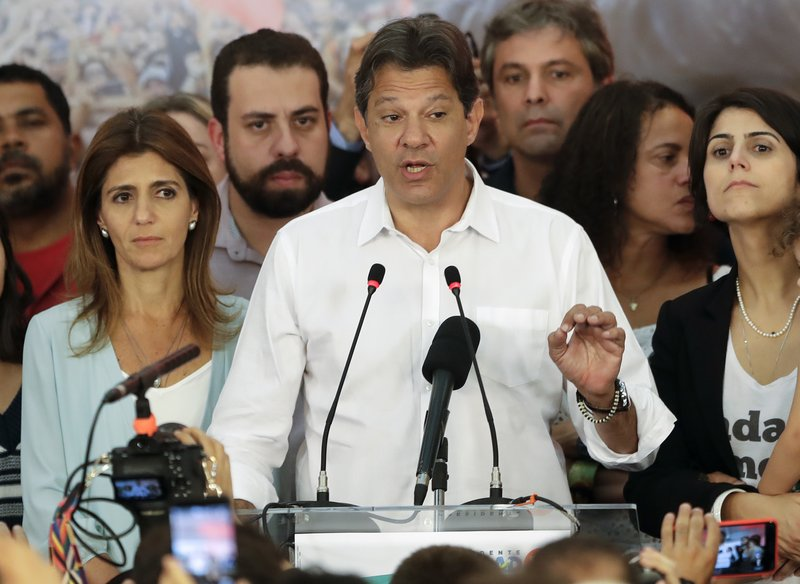 Flanked by his wife Ana Estela, left, and running mate Manuela d'Avila, Workers' Party presidential candidate Fernando Haddad delivers his concession speech, in Sao Paulo, Brazil, Sunday, Oct. 28, 2018. Brazil's Supreme Electoral Tribunal declared far-right congressman Jair Bolsonaro the next president of Latin America's biggest country. (AP Photo/Andre Penner)