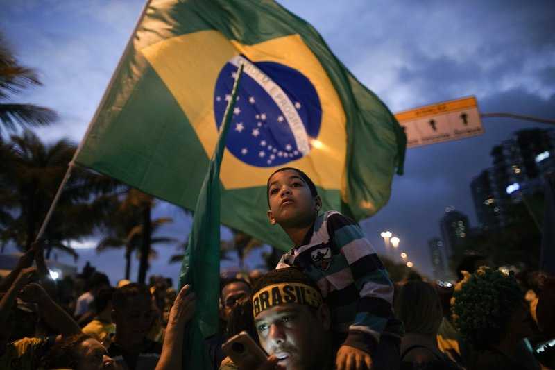 Supporters gather outside the residence of presidential candidate Jair Bolsonaro in anticipation of his victory speech, in Rio de Janeiro, Brazil, Sunday, Oct. 28, 2018. Brazil's Supreme Electoral Tribunal declared the far-right congressman the next president of Latin America's biggest country. (AP Photo/Leo Correa)
