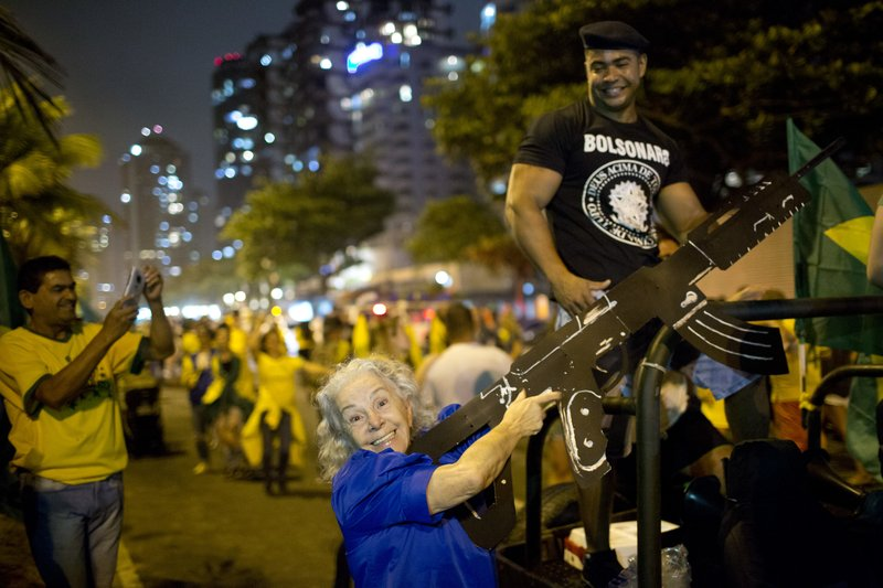 A supporter of presidential candidate Jair Bolsonaro poses for a photo with an oversized, fake rifle, as she celebrates the election runoff results in Rio de Janeiro, Brazil, Sunday, Oct. 28, 2018. Brazil's Supreme Electoral Tribunal declared the far-right congressman the next president of Latin America's biggest country. (AP Photo/Silvia Izquierdo)