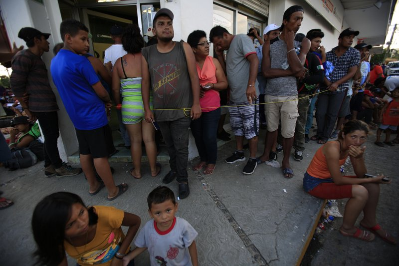 Migrants wait in a slow-moving line to collect money transfers sent by relatives back home, as a caravan of Central Americans trying to reach the U.S. border halts for a rest day in Tapanatepec, Oaxaca state, Mexico, Sunday, Oct. 28, 2018. Thousands of Central American migrants took a break Sunday on their long journey toward the U.S. border roughly 1000 miles away, with Mexican government agencies seeming to waver between helping and hindering. (AP Photo/Rebecca Blackwell)