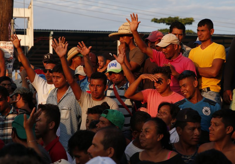 Migrants raise their hands to call for silence as volunteers try to organize the distribution of donated food, in Tapanatepec, Mexico, where a caravan of Central Americans trying to reach the U.S. border halted for a rest day on Sunday, Oct. 28, 2018. Thousands of migrants took a break Sunday on their long journey toward the U.S. border roughly 1000 miles away, with Mexican government agencies seeming to waver between helping and hindering.(AP Photo/Rebecca Blackwell)