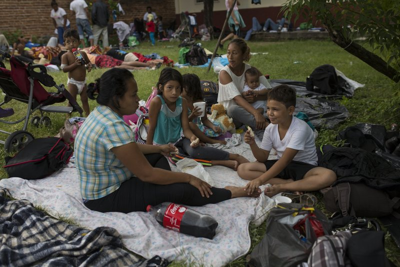 Migrants who are part of a caravan of Central Americans trying to reach the U.S. border eat breakfast, in Tapanatepec, Mexico, Sunday, Oct. 28, 2018. Thousands of migrants took a break Sunday on their long journey toward the U.S. border. (AP Photo/Rodrigo Abd)