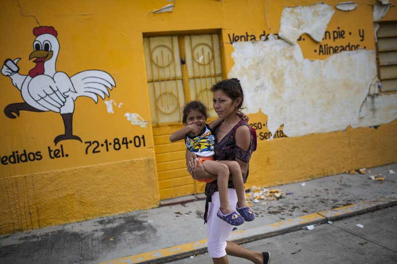 Migrant Yesenia Nieto carries her daughter Britany, as they go in search of food, in Tapanatepec, Mexico, Sunday, Oct. 28, 2018. Thousands of migrants who are part of a caravan of Central Americans trying to reach the U.S. border took a break Sunday on their long journey toward the U.S. border. (AP Photo/Rodrigo Abd)
