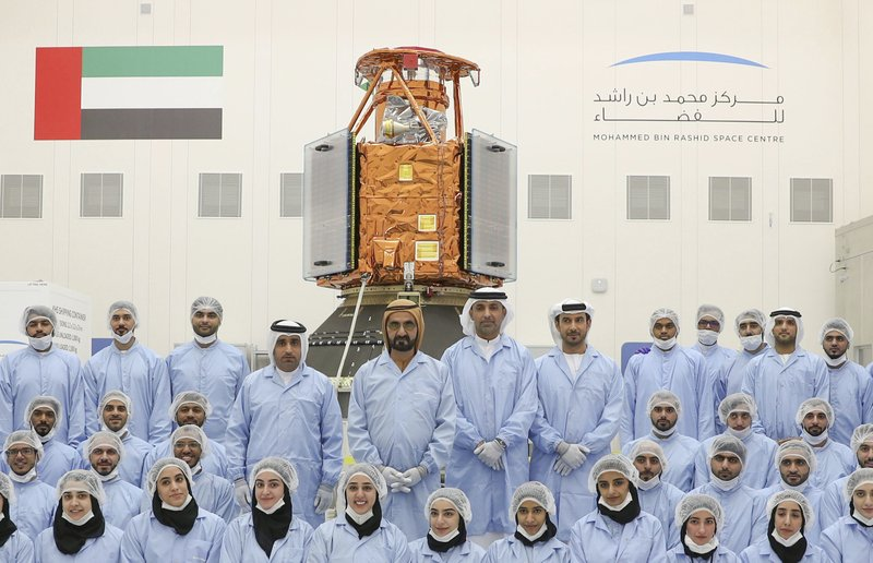 In this undated photograph released Feb. 2, 2018 by the state-run Emirates News Agency (WAM), Sheikh Mohammed bin Rashid Al Maktoum, Dubai's ruler and the vice president and prime minister of the United Arab Emirates, center back row, visits the Mohammed bin Rashid Space Center to see the locally made KhalifaSat satellite in Dubai, United Arab Emirates. A Japanese rocket carrying the United Arab Emirates' first locally-made satellite has successfully lifted off from a space center in southern Japan Monday, Oct. 29, 2018. (WAM via AP)