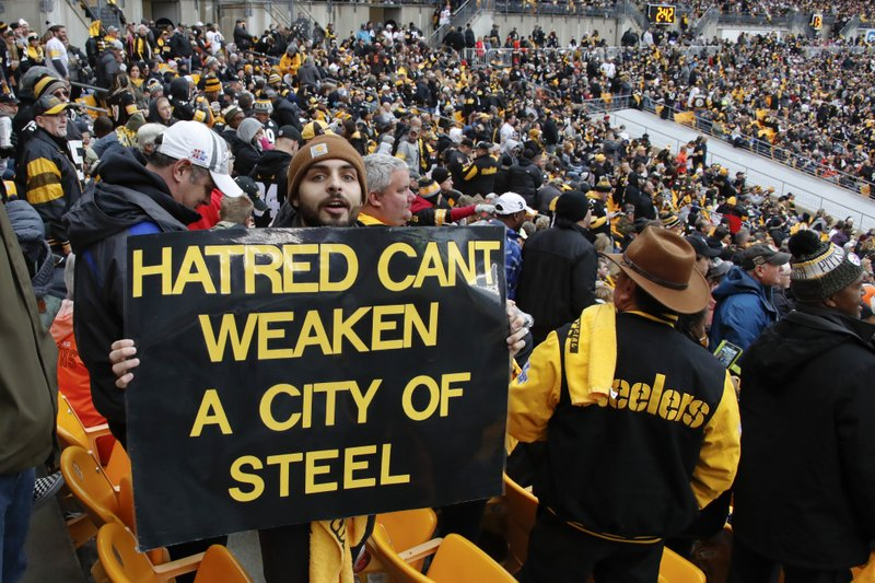 A Pittsburgh Steelers fan holds a sign honoring the victims of a deadly shooting spree at a synagogue on Saturday during the second half of an NFL football game between the Pittsburgh Steelers and the Cleveland Browns, Sunday, Oct. 28, 2018, in Pittsburgh. (AP Photo/Gene J. Puskar)