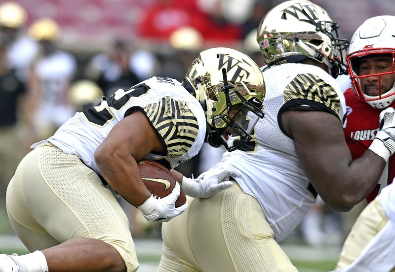 Wake Forest running back Matt Colburn (22) runs behind blockers during the second half of an NCAA college football game against Louisville, Saturday, Oct. 27, 2018, in Louisville, Ky. Wake Forest won 56-35. (AP Photo/Timothy D. Easley)