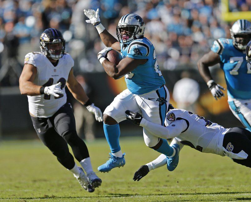 Carolina Panthers' C.J. Anderson (20) runs as Baltimore Ravens' Patrick Ricard (42) nurses in the second half of an NFL football game in Charlotte, N.C., Sunday, Oct. 28, 2018. (AP Photo/Nell Redmond)