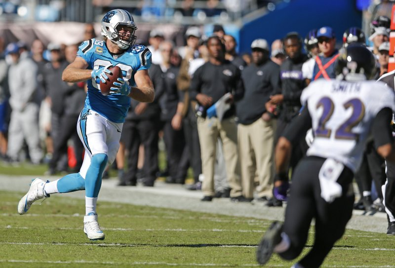 Carolina Panthers' Greg Olsen (88) runs after a catch as Baltimore Ravens' Jimmy Smith (22) defends in the first half of an NFL football game in Charlotte, N.C., Sunday, Oct. 28, 2018. (AP Photo/Nell Redmond)