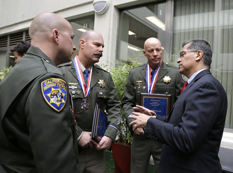 Attorney General Xavier Becerra, right, talks with California Highway Patrol officers Phil Agdeppa, left, Pete Gavitte, second from left, and Chad Millward, third from left, after they were award the public safety officer's Medal of Valor Monday, Oct. 29, 2018, in Sacramento, Calif. The three officers were honored by Gov. Jerry Brown for their actions in saving nearly four dozen people during last year's wine country wildfire near Napa. (AP Photo/Rich Pedroncelli)