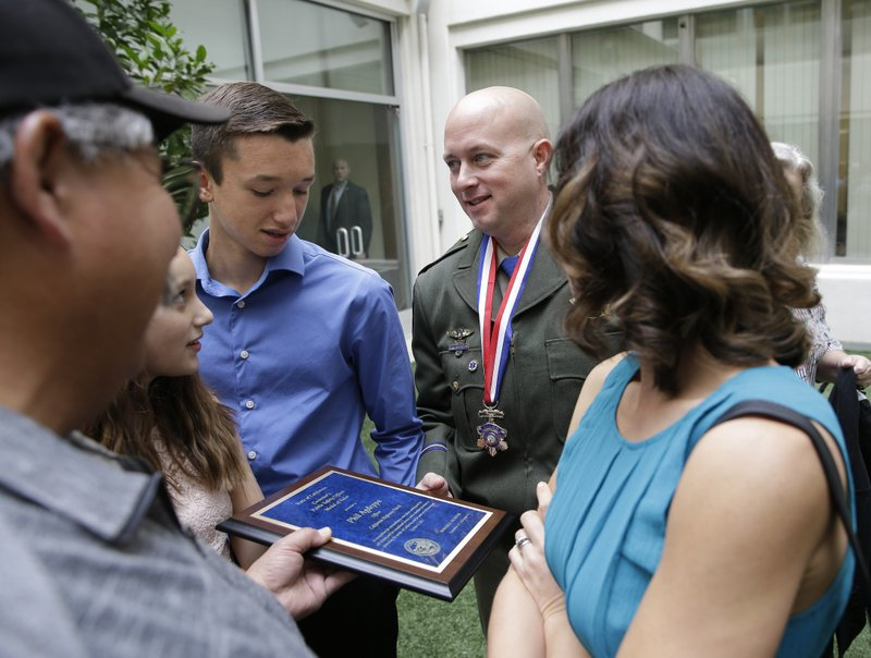 California Highway Patrol Officer Phil Agdeppa shows his family the plaque he was given after he was one of five public safety officers awarded the Medal of Valor Monday, Oct. 29, 2018, in Sacramento, Calif. Agdeppa and three other CHP officers received the award from Gov. Jerry Brown for their actions in saving nearly four dozen people during last year's wine country wildfire near Napa. Seen from left are Agdeppa's family, father, Marty, daughter Mackenzie, son, Colton and wife Gypsie,right. (AP Photo/Rich Pedroncelli)