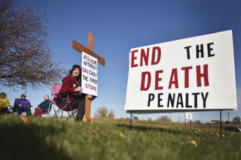 Elaine Engelgau holds a sign outside of the South Dakota State Penitentiary in Sioux Falls, S.D., before Rodney Berget is executed Monday, Oct. 29, 2018. The U.S. Supreme Court cleared the way Monday for the execution of the South Dakota man who killed a prison guard in a failed escape seven years ago after a last-minute legal bid to block Berget's death delayed his execution for hours past its scheduled time. (Briana Sanchez/The Argus Leader via AP)