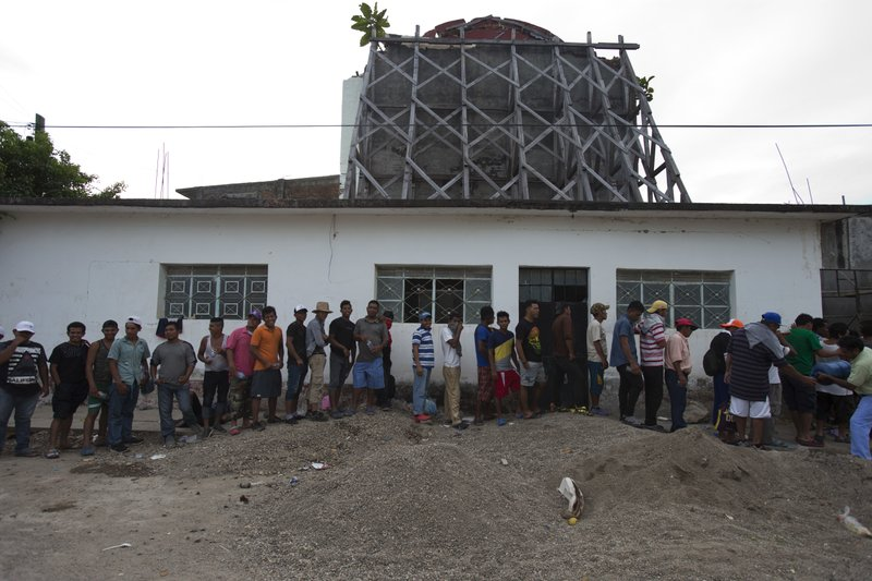 Migrants line up to receive food handouts in front of the backside of a church heavily damaged in a Sept. 7, 2017 earthquake, as a thousands-strong caravan of Central Americans hoping to reach the U.S. border stops for the night in Niltepec, Oaxaca state, Mexico, Monday, Oct. 29, 2018. As the caravan resumed its slow advance Monday, still at least 1000 miles or farther from the U.S., the Pentagon announced it would send 5,200 active-duty troops to