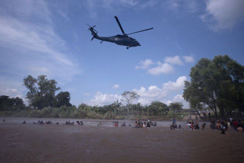 A Mexican Federal Police helicopter flies close to the Suchiate River that connects Mexico and Guatemala, in order to create a downwash force to discourage a new group of Central American migrants bound for the U.S border, in wading across the river, in Tecun Uman, Guatemala, Monday, Oct. 29, 2018. The first group was able to cross the river on rafts — an option now blocked by Mexican Navy river and shore patrols. (AP Photo/Santiago Billy)