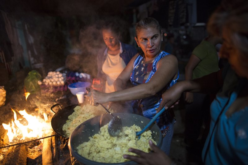 Women cook dinner for Hondura's migrants at a makeshift shelter in Ciudad Hidalgo, Mexico, Monday, Oct. 29, 2018. A second group of Hondura's migrants was able to cross the Suchiate river on rafts — an option now blocked by Mexican Navy river and shore patrols. (AP Photo/Rodrigo Abd)