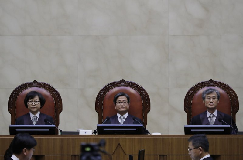 South Korean Chief Justice of the Supreme Court KIM Myeongsu, center, sits with other justices upon their arrival at the Supreme Court in Seoul, South Korea, Tuesday, Oct. 30, 2018. South Korea's Supreme Court has ruled that a Japanese steelmaker should compensate four South Koreans for forced labor during Japan's colonial rule of the Korean Peninsula before the end of World War II. (AP Photo/Lee Jin-man)
