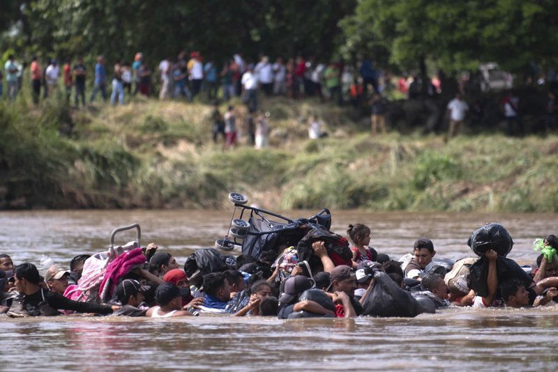 A new group of Central American migrants wade in mass across the Suchiate River, that connects Guatemala and Mexico, in Tecun Uman, Guatemala, Monday, Oct. 29, 2018. The first group was able to cross the river on rafts — an option now blocked by Mexican Navy river and shore patrols. (AP Photo/Santiago Billy)