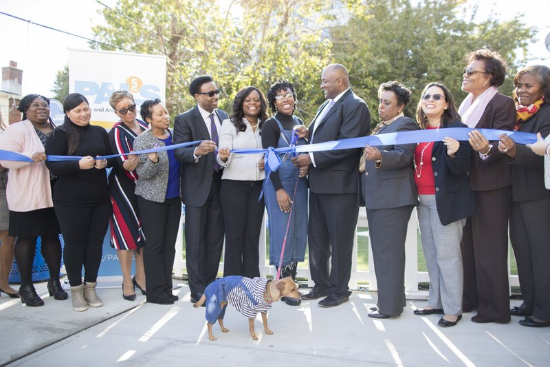 President and CEO of the Urban Resource Institute, Nathaniel Fields, fifth from left, is joined by survivors of domestic violence, local officials, and staff during a ribbon cutting ceremony for a pet friendly domestic violence shelter, Tuesday, Oct. 30, 2018, in New York. The shelter, custom-designed for domestic violence victims to keep their pets in their apartments, has been built in New York City. Organizers say it's the first custom-built, pet-friendly shelter of its size. (AP Photo/Mary Altaffer)